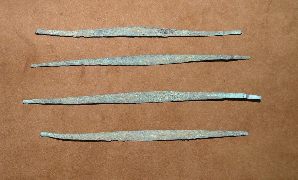Abb.3: Vier flache, stabförmige, etwas gewellte, spitz auslaufende Kupferbarren der Sundi. Länge zwischen 17 und 19,5 cm, Gewicht von 14,6 bis 20,7 g.