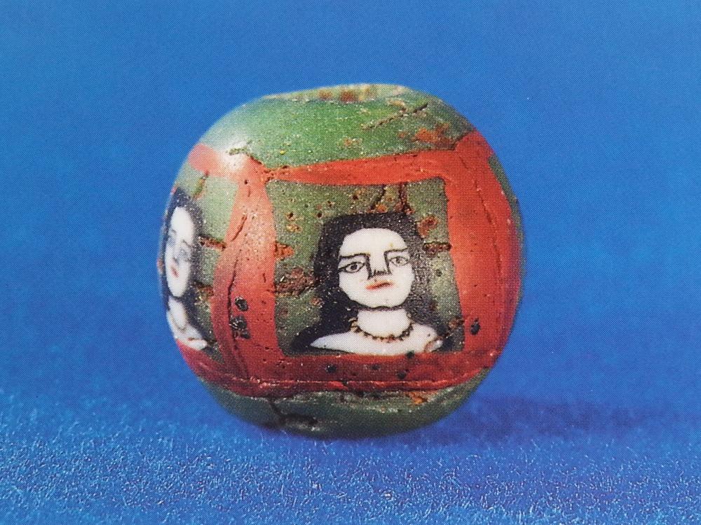 """florale und figürliche Murrinen sind jedenfalls seit dem 8.Jahrhundert vor Christus bekannt. Diese Perle mit """"Gesichts-Murrinen"""" stammt aus dem 1.Jahrhundert nach Christus (Abb. 149 aus E.Marianne Stern, Birgit Schlick-Nolte, 1964, Frühes Glas der alten Welt)."""